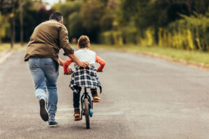 Father helping son to ride bike