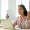 Woman smiling and holding paper on laptop