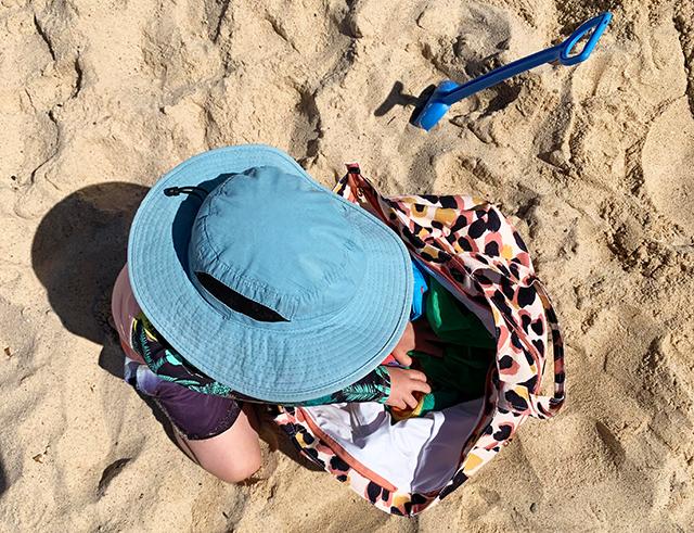 Boy looking in bag on beach