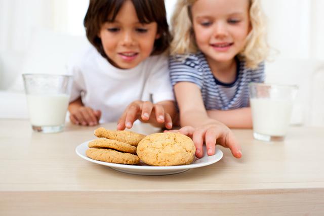 Siblings eating biscuits