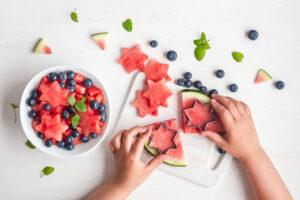 Child cutting watermelon shapes