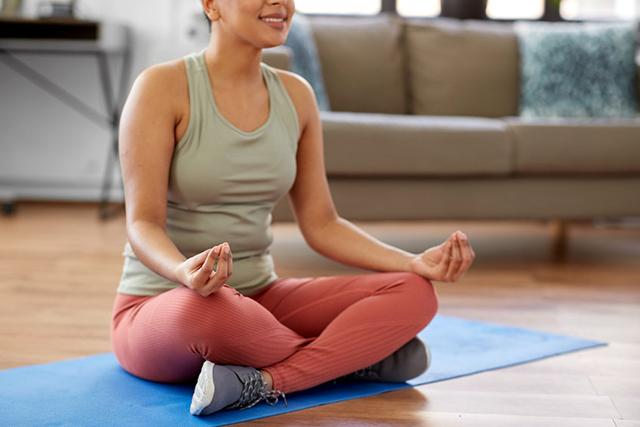 woman meditating in yoga lotus pose at home